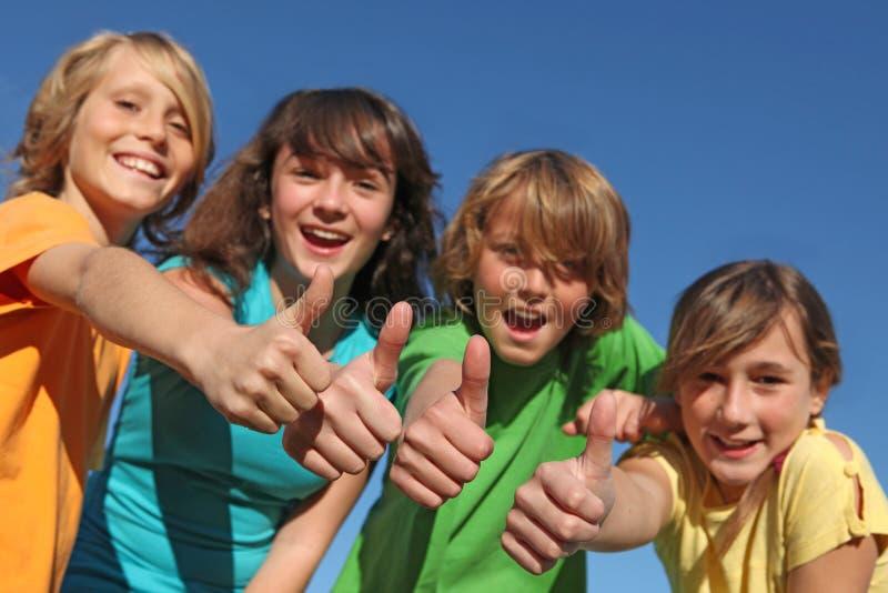 Grupo de tweens dos miúdos com polegares acima foto de stock