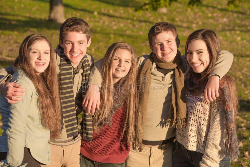 Grupo de um abraço de cinco adolescentes foto de stock