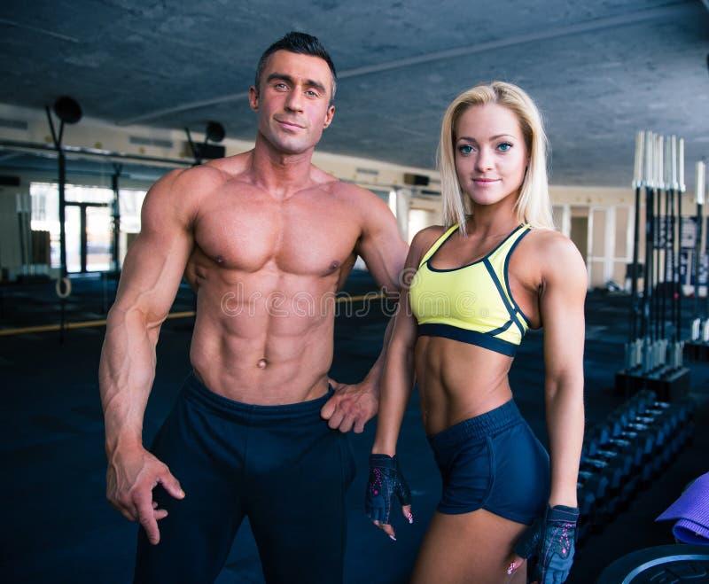 Grupo de um homem e de uma mulher no gym do crossfit fotos de stock