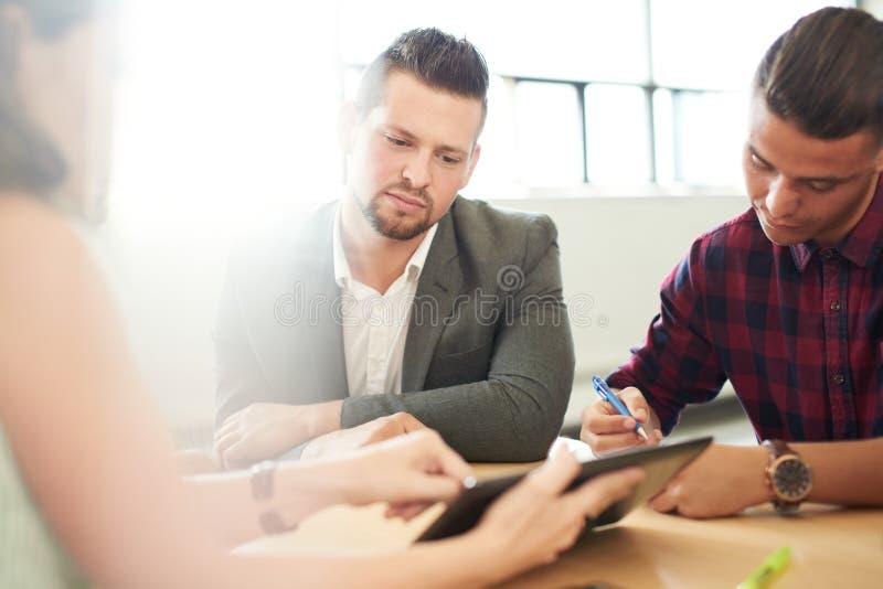 Grupo de Unposed de empresarios de negocio creativos en una oficina abierta del concepto que se inspiran junto en una tableta dig fotografía de archivo