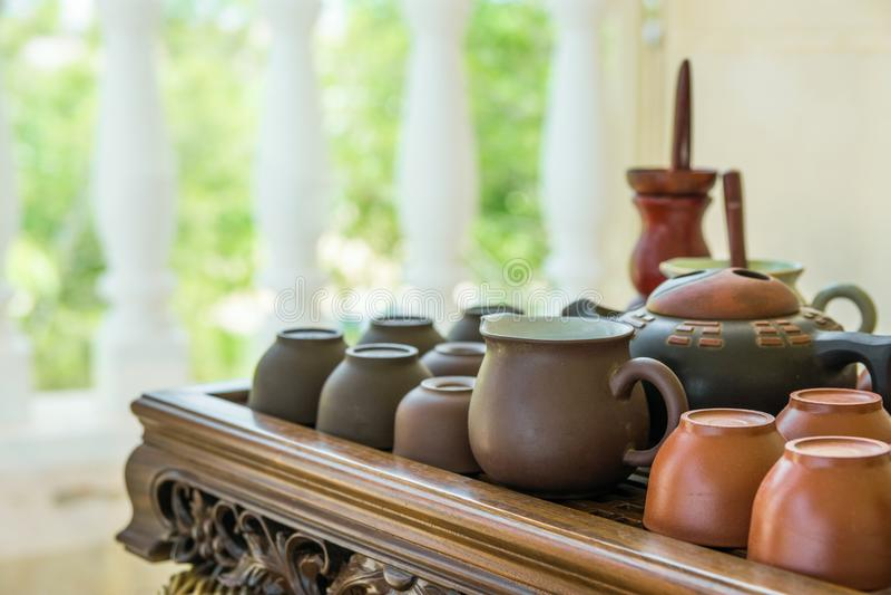 Grupo de utensílios japoneses chineses das bacias do potenciômetro dos copos de chá na bandeja de madeira de bambu no terraço da  imagem de stock royalty free