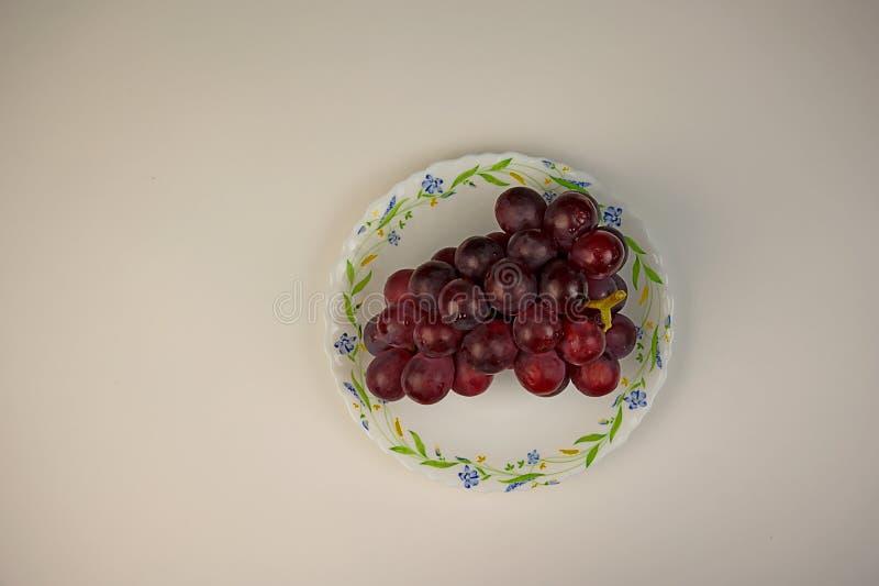 Grupo de uvas com gotas da ?gua na placa branca fotos de stock