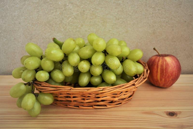 Grupo de uvas em uma cesta de vime e em uma maçã fotografia de stock royalty free