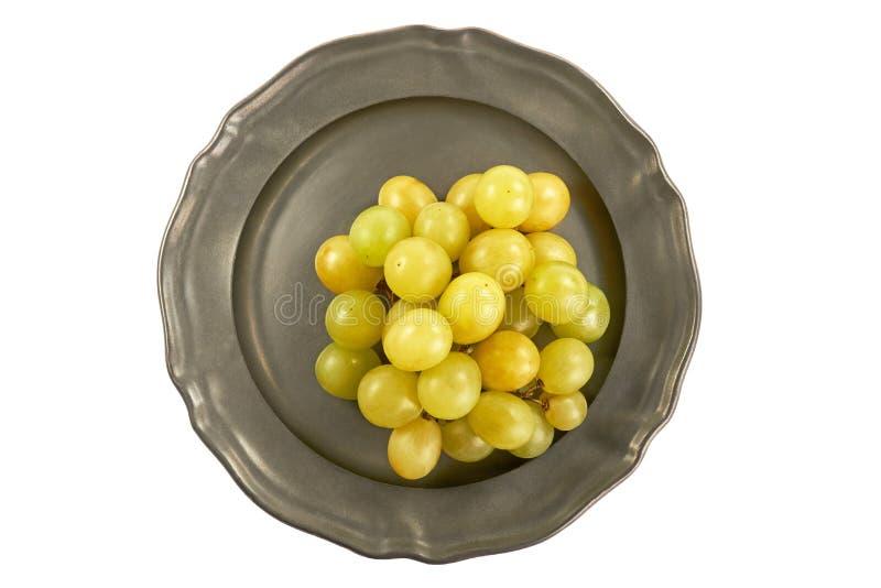 Grupo de uvas verdes em uma placa de metal, centralmente, de cima sobre de um fundo branco fotos de stock royalty free