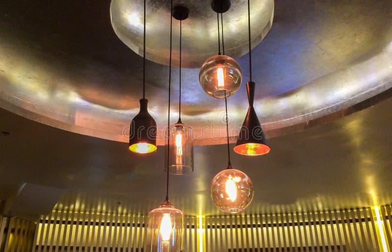 Grupo de vário metal moderno do preto do estilo e de lâmpadas iluminadas vidro que penduram no teto fotos de stock royalty free