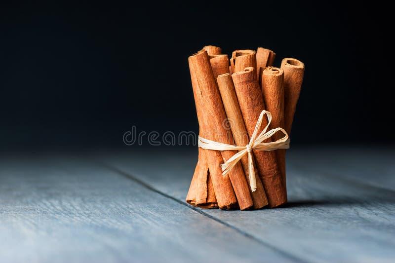 Grupo de varas de canela amarradas na tabela rústica de madeira cinzenta preta foto de stock