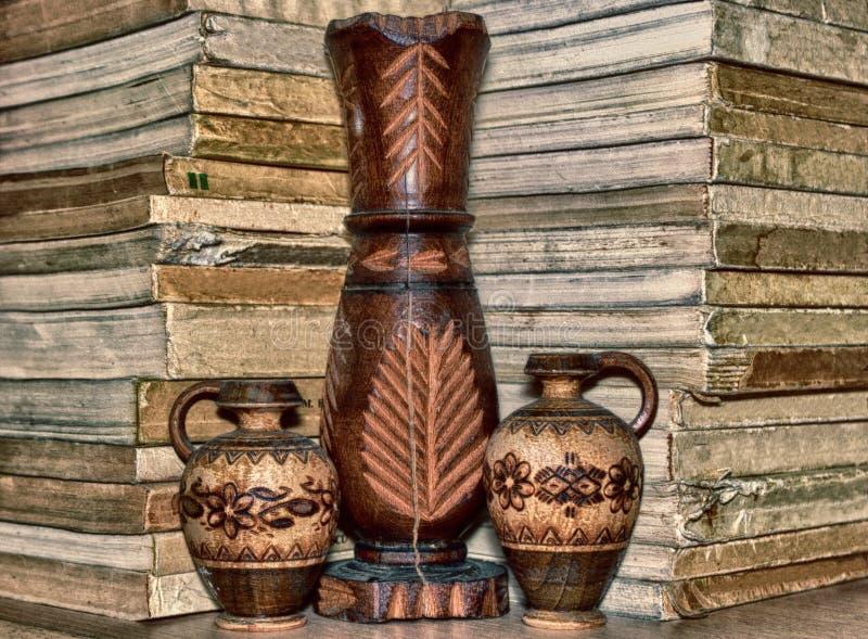 Grupo de vaso e de copos de madeira em uma prateleira com livros fotografia de stock royalty free