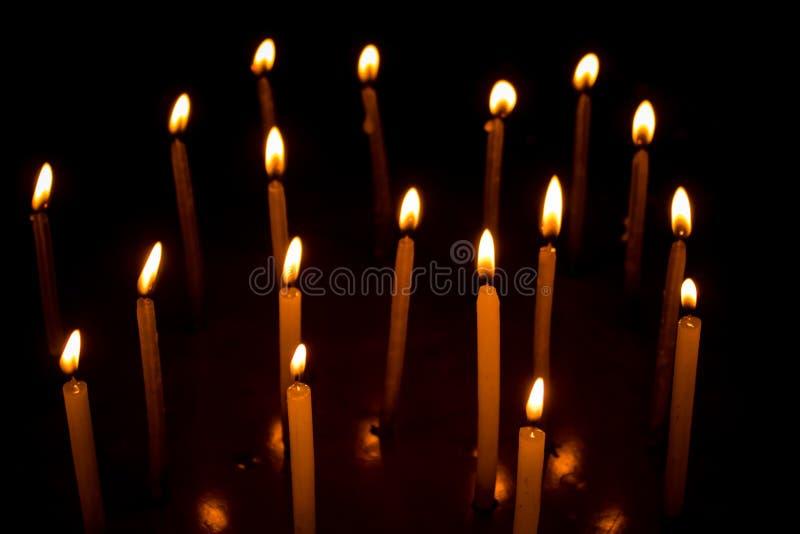 Grupo de velas ardientes en oscuridad fotografía de archivo libre de regalías