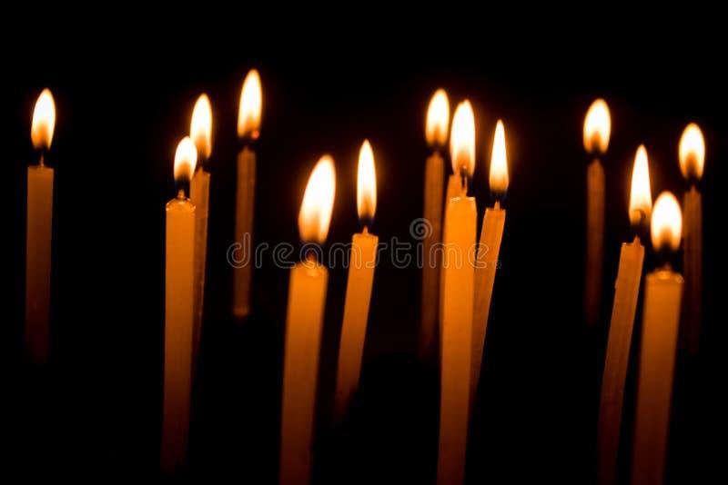 Grupo de velas ardientes en oscuridad fotografía de archivo