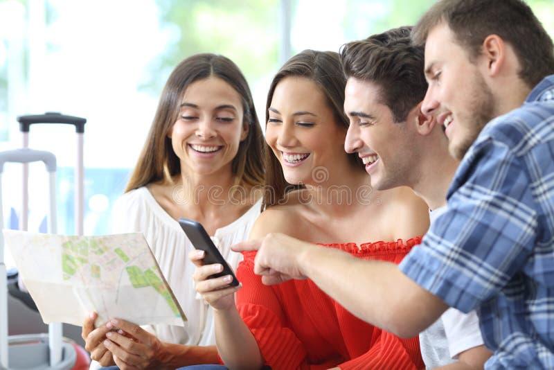 Grupo de viaje de la planificación turística en línea en el teléfono fotografía de archivo