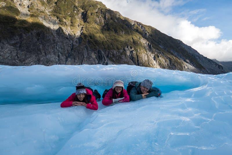 Grupo de viajeros que ponen debajo de un arco del hielo en el glaciar del Fox en Nueva Zelanda imagen de archivo libre de regalías