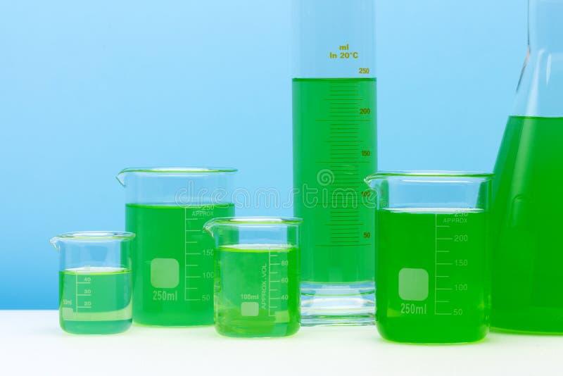 Grupo de vidro do laboratório enchido com a substância verde imagem de stock