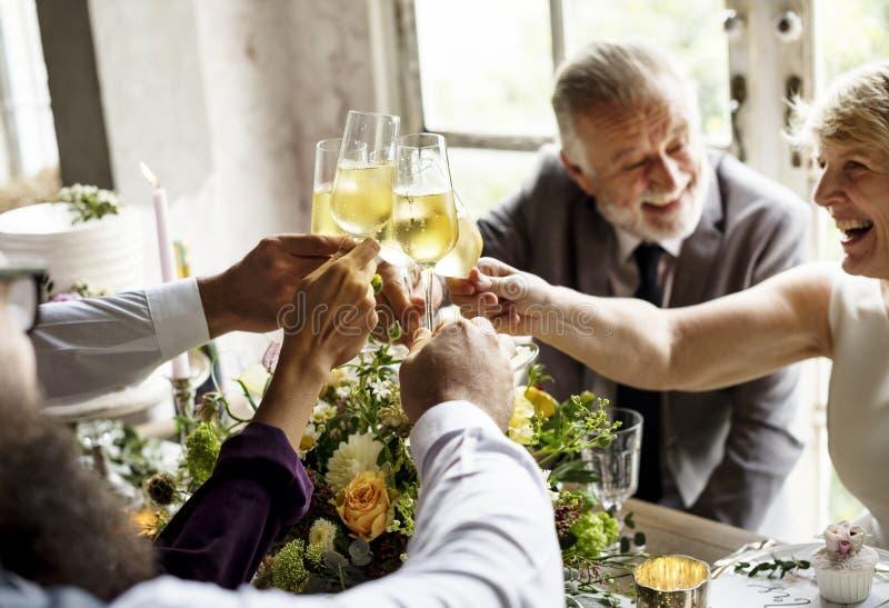 Grupo de vidros de vinho diversos junto Congratul do tinido dos povos fotografia de stock royalty free