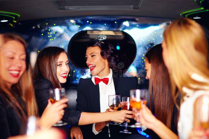 Grupo de vidros felizes do tinido das mulheres elegantes na limusina, partido de galinha fotografia de stock royalty free