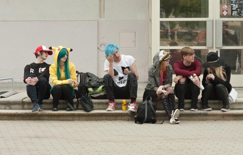 Grupo de visitantes que se sientan en las escaleras en Animefest fotografía de archivo