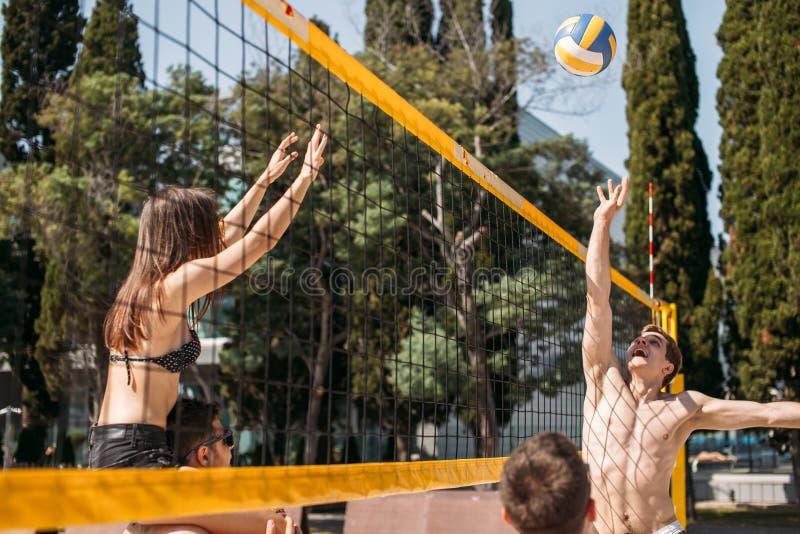 Grupo de voleibol de jogo de descanso na corte da praia fotos de stock