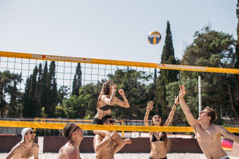 Grupo de voleibol de jogo de descanso na corte da praia fotografia de stock