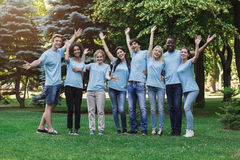 Grupo de voluntários dos jovens que abraçam no parque imagem de stock