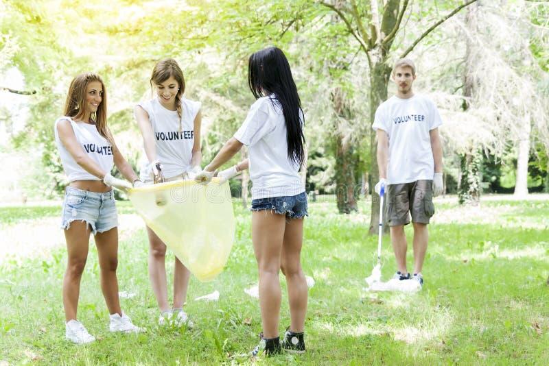 Grupo de voluntários novos que pegaram a maca no parque fotos de stock