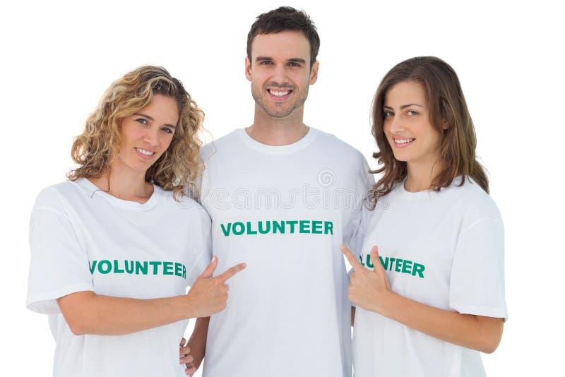 Grupo de voluntários que apontam seu tshirt foto de stock