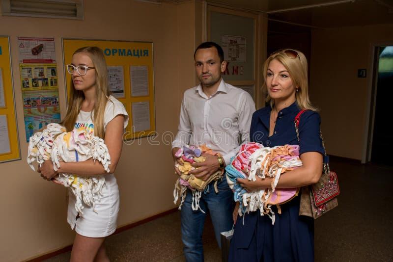 Grupo de voluntários que doam a roupa para bebês no hospital de maternidade durante o dia da proteção das crianças imagens de stock royalty free
