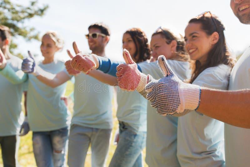 Grupo de voluntários que mostram os polegares acima fora foto de stock
