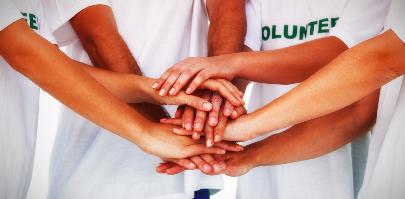 Grupo de voluntários que unem as mãos fotografia de stock