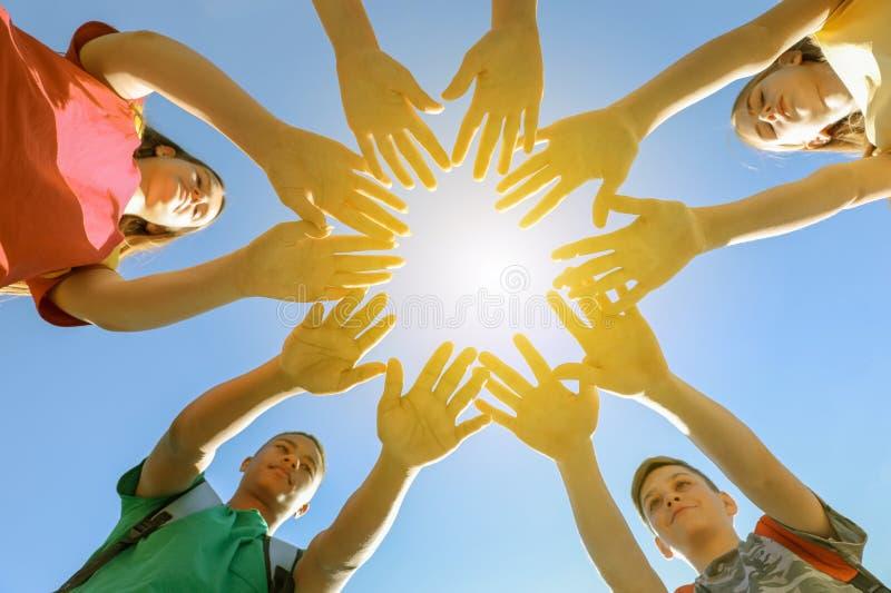 Grupo de voluntários que unem as mãos fora imagens de stock