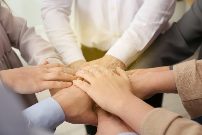 Grupo de voluntários que unem suas mãos imagem de stock