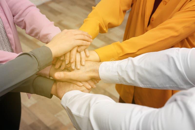 Grupo de voluntários que unem suas mãos, close up fotografia de stock