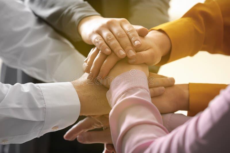 Grupo de voluntários que unem suas mãos, close up imagens de stock royalty free