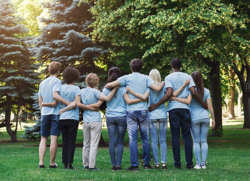 Grupo de voluntarios felices que abrazan en parque foto de archivo libre de regalías