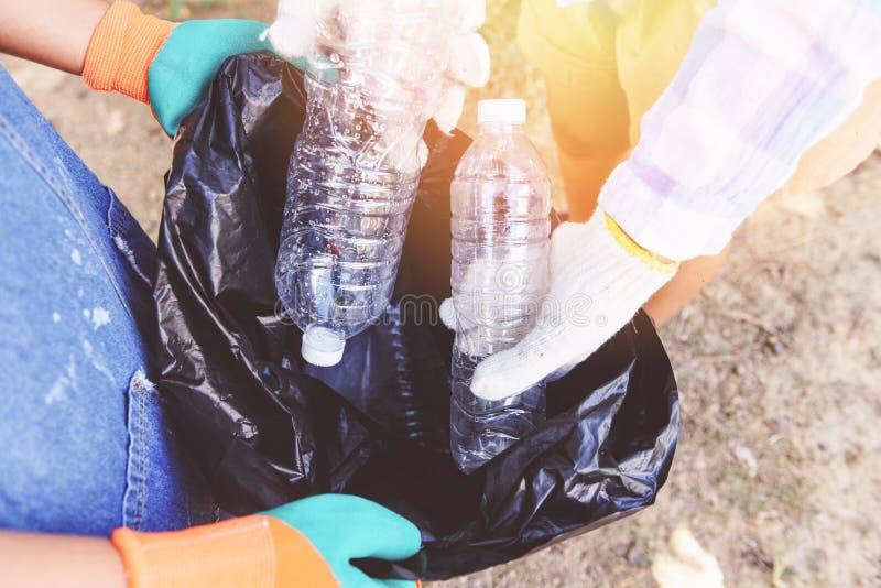 Grupo de voluntarios de las mujeres jovenes que ayudan a mantener la naturaleza limpia y que cogen la botella plástica de la basu imagenes de archivo
