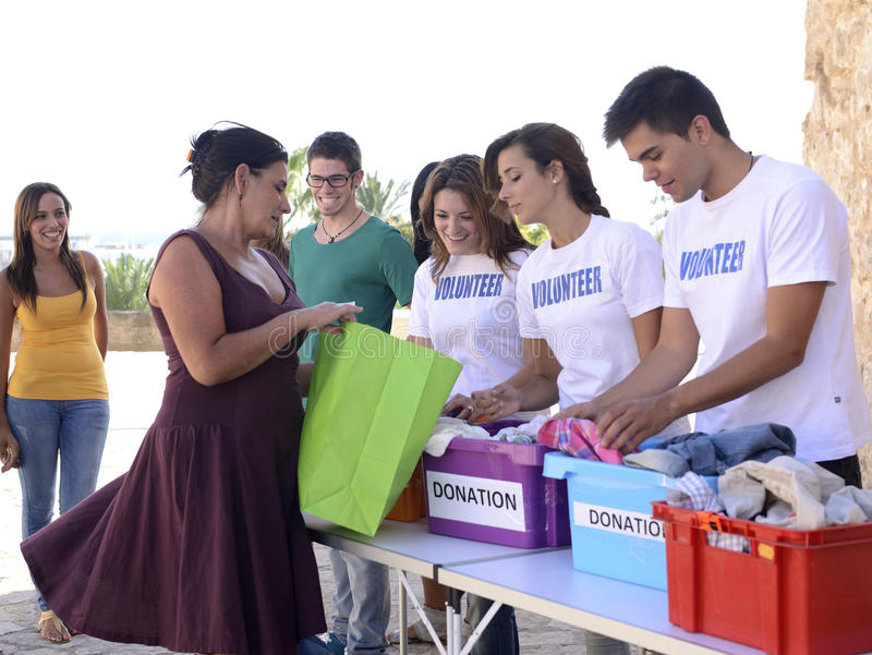 Grupo de voluntarios que recogen donaciones de la ropa fotos de archivo