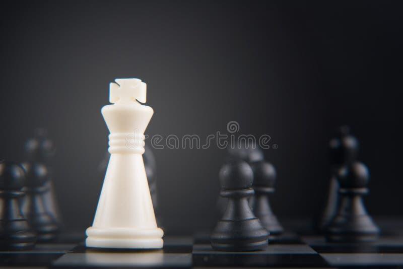 Grupo de xadrez no tabuleiro de xadrez rei branco contra o penhor preto imagem de stock royalty free