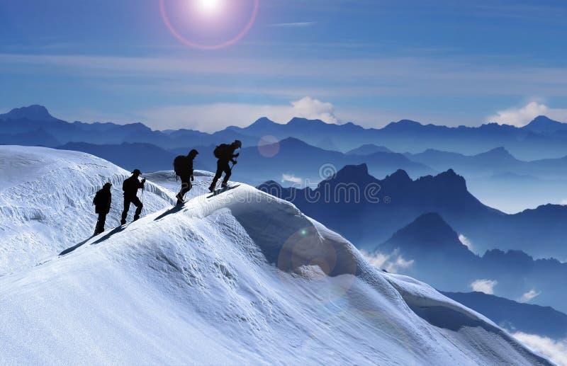 Grupo del alpinismo en pico nevoso foto de archivo libre de regalías