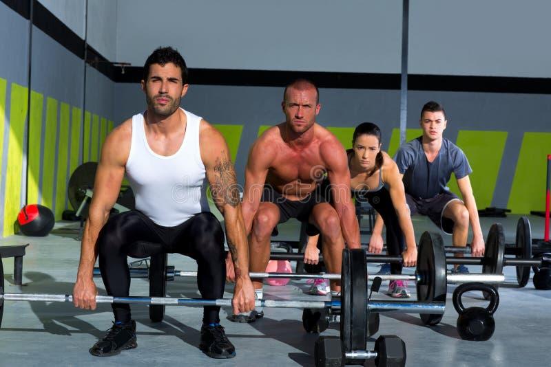 Grupo del gimnasio con entrenamiento del crossfit de la barra del levantamiento de pesas fotografía de archivo libre de regalías