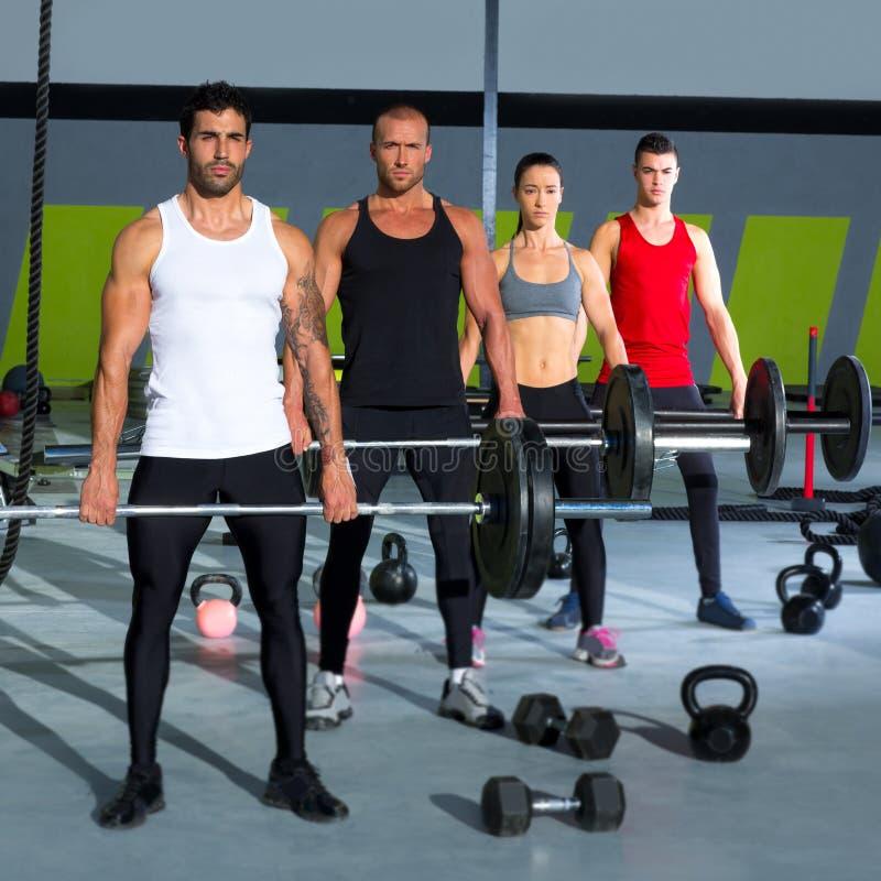 Grupo del gimnasio con entrenamiento del crossfit de la barra del levantamiento de pesas fotografía de archivo