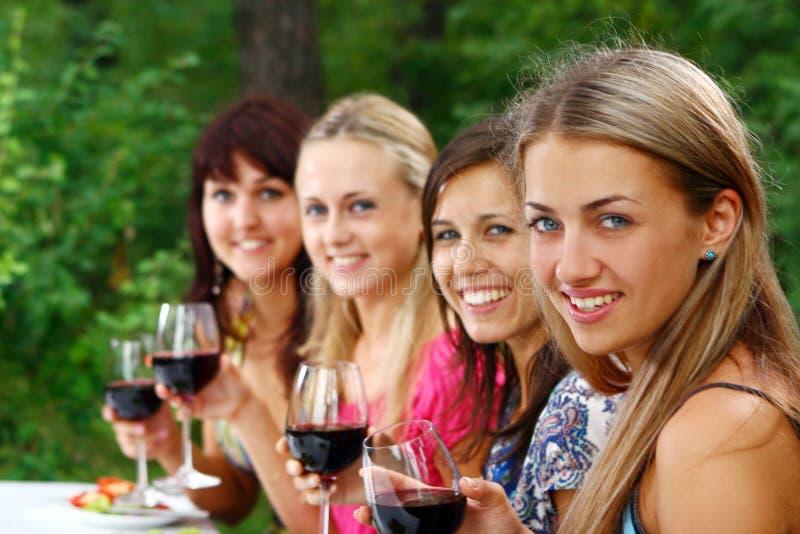 Grupo del vino de consumición de las mujeres jovenes fotos de archivo