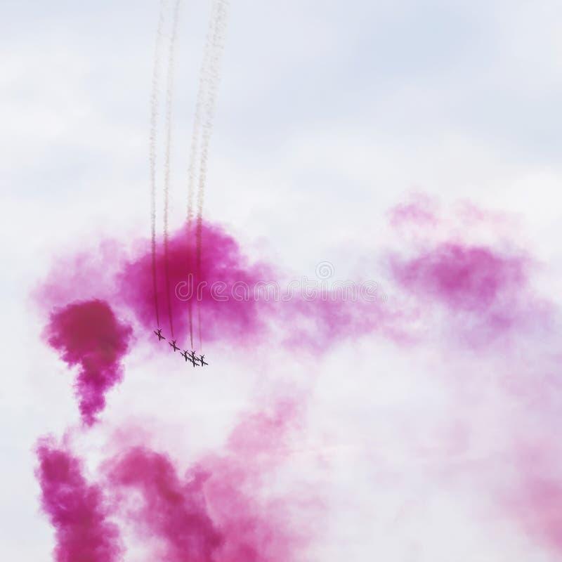Grupo del vuelo en brillante, anillo del humo, color de los aviones de la sangría Aeroplanos en la demostración aeroacrobacia Fun foto de archivo