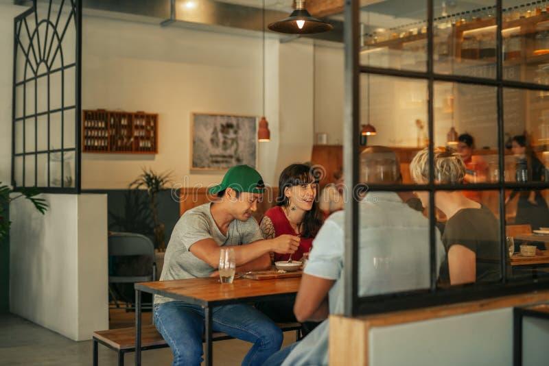 Grupo diverso de amigos que comen junto en un bistro imagenes de archivo
