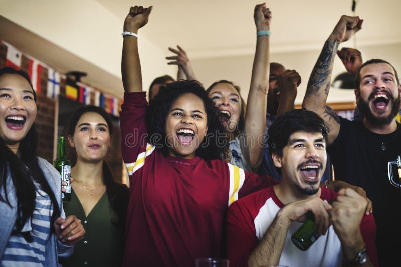 Grupo diverso de amigos que olham o jogo dos esportes junto imagem de stock royalty free