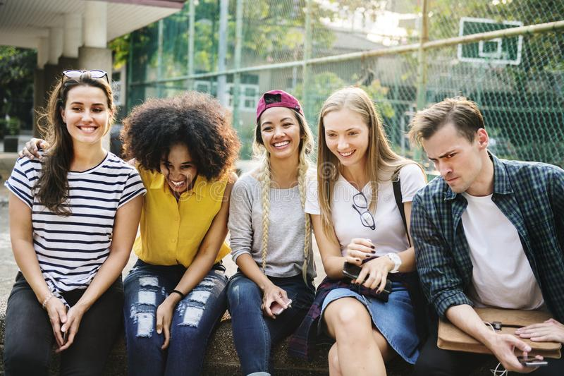 Grupo diverso de amigos que penduram para fora nos millennials do parque e no conceito da cultura de juventude imagens de stock