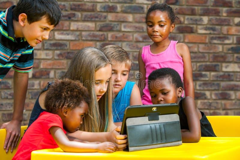 Grupo diverso de crianças que olham a tabuleta.