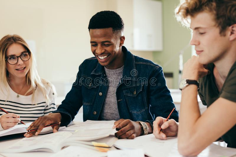 Grupo diverso de estudantes que discutem em notas imagem de stock