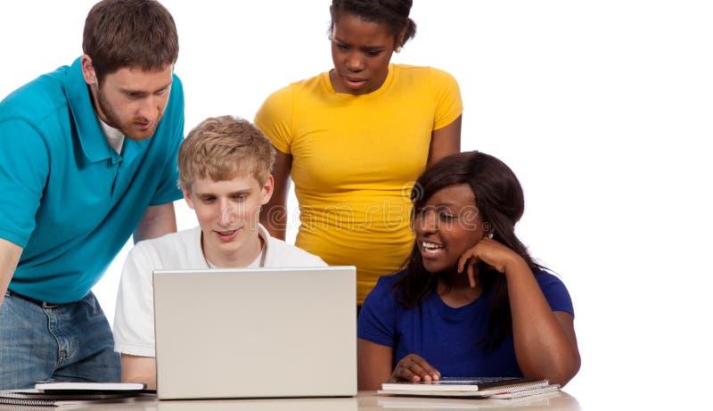 Grupo diverso de estudiantes universitarios/de amigos que miran un ordenador foto de archivo libre de regalías