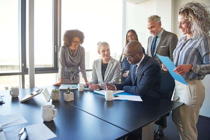 Grupo diverso de executivos que trabalham junto em torno de uma sala de reuniões imagens de stock