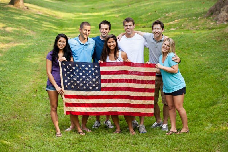 Grupo diverso de jovens com bandeira americana fotografia de stock