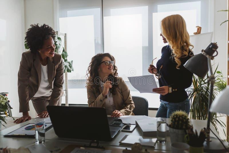 Grupo diverso de mujeres de negocios sonrientes que tienen una rotura en hablar de la oficina fotos de archivo libres de regalías