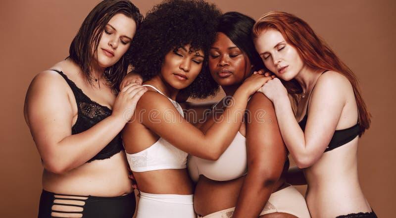 Grupo diverso de mulheres na roupa interior junto imagens de stock royalty free